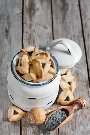 hamantasch: Hamantaschen cookies or Hamans ears - triangle cookies stuffed with poppy seeds, traditioal food on Purim, judaic holiday. Copy space background. Stock Photo