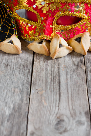 megillah: Hamantaschen cookies or Hamans ears and carnival masks for Purim celebration (jewish holiday). Copy space background. Stock Photo