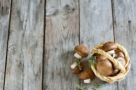 Fresh raw portabello mushrooms in wicker basket on dark wooden background photo