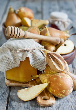 Ripe yellow pears and jars of honey on old wooden background photo