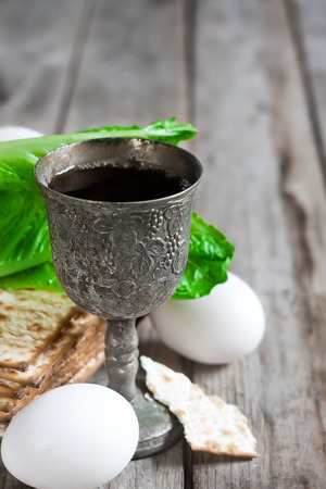 matzot: Wine, egg, bitter salad leaves, matzot - traditional jewish passover celebration elements. Copy space background.