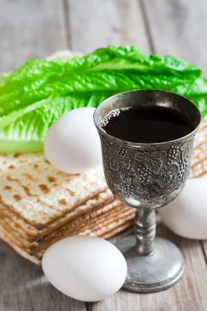kiddush: Wine, egg, bitter salad leaves, matzot - traditional jewish passover celebration elements.