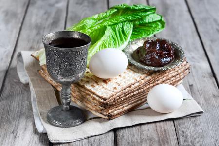 Wine, egg, bitter salad leaves, matzot and haroset - traditional jewish passover celebration elements.