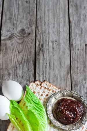 passover: Egg, bitter salad leaves, matzot and haroset - traditional jewish passover celebration elements. Copy space background. Stock Photo