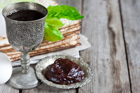 jewish food: Wine, egg, bitter salad leaves, matzot and haroset - traditional jewish passover celebration elements. Copy space background. Stock Photo