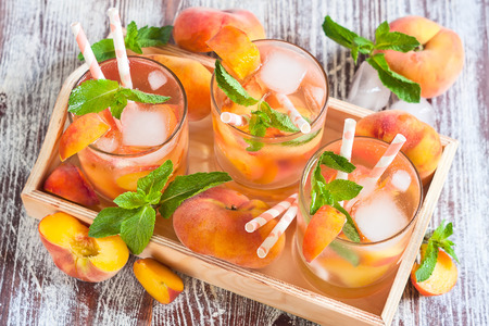 Homemade lemonade with ripe flat saturn-shaped peaches and fresh mint