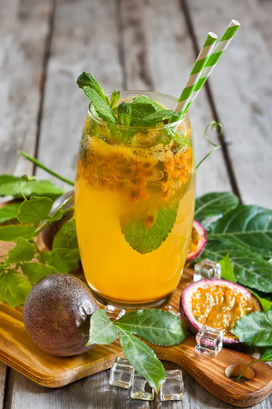 Homemade lemonade with passionfruit, mint leaves and ice cubes on old wooden background