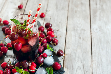 Cherry juice with ice cubes, mint leaves and ripe sweet cherry. Copy space background.