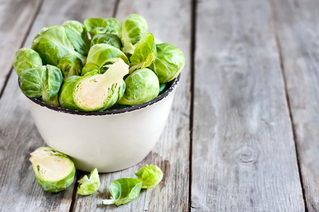 Brussels sprout in small rustic bowl on old wooden table.