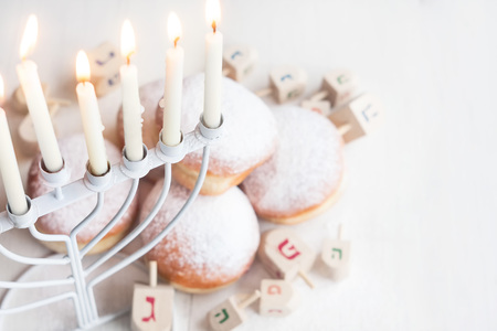hanukka: Jewish traditional holiday Hannukah with menorah, doughnuts and dreidles. Copy paste background. Stock Photo