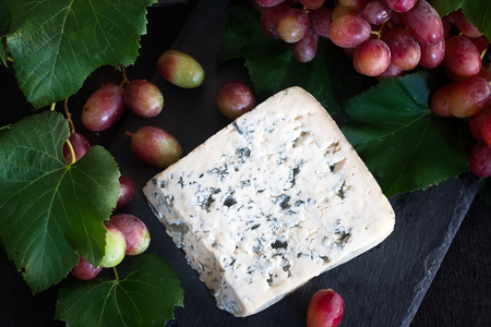 stilton: Blue cheese Dorblu with red grape on black background