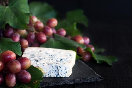 tabla de quesos: Dorblu queso azul con uva roja sobre fondo negro