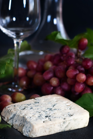 tabla de quesos: Blue cheese Dorblu with red grape on black background