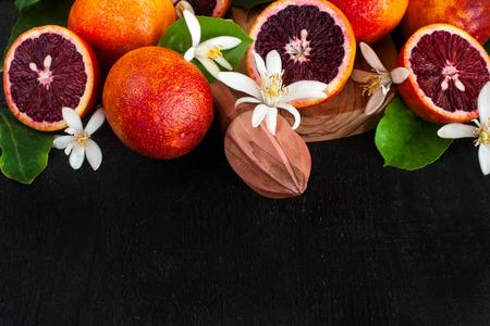 Laranja de sangue fresco decorada com flor de laranjeira. Foto de baixa chave. Copie o fundo do espaço. Foto de archivo - 75846185