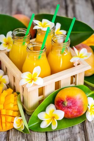 Fresh mango juice in small bottles in wooden box