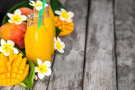 Fresh mango juice in small bottles. Copyspace background.
