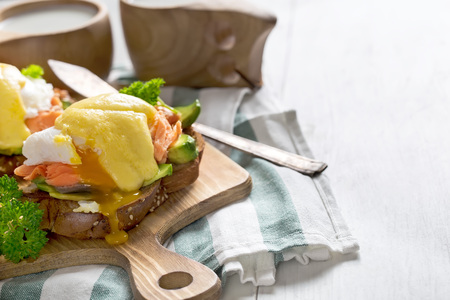 Eggs benedict, scandinavian style - with avocado and poached salmon. Copy space background. High key.