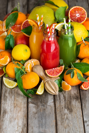 Fresh orange, blood orange juice and homemade lemonade in small bottles on old wooden table. Copy space background. Stock Photo