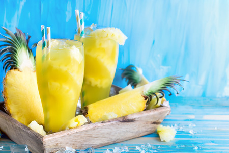 Pineapple juice and fresh ripe pineapple on wooden background Stock Photo