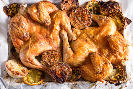 Flattaned out roasted golden chicken with lemon and garlic. Top view. Stock Photo