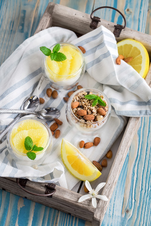 Yogurt with granola, almonds and grapefruit slices on old wooden background Stock Photo