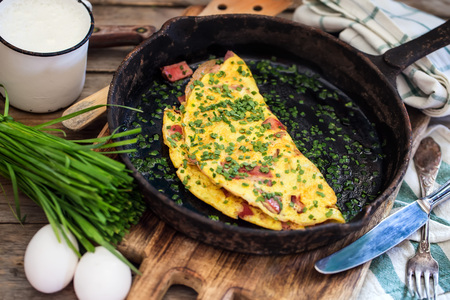 Cast iron frypan with omlette with ham and chives on old wooden background. Rustic style.
