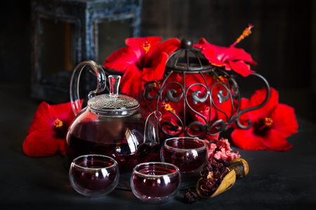 Herbal hibiscus tea carcade with red hibiscus flowers. Dark mood photo. Stock Photo