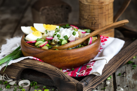 Russian traditional cold soup okroshka with potato, ham, cucmebers, eggs, radish, spring onion and kvass. Stock Photo