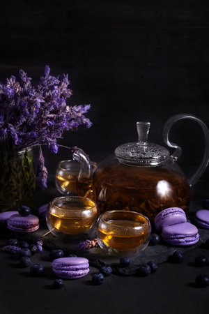 Tea in the glass teapot with lavender and blueberry macarons Stock Photo