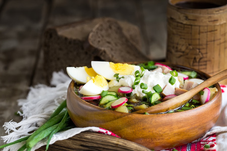 Russian traditional cold soup okroshka with potato, ham, cucmebers, eggs, radish, spring onion and kvass. Copyspace background. Stock Photo