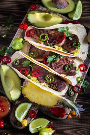 Traditional mexican street food - beef tongue tacos with ananas salsa and guacamole Stock Photo