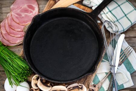 Empty frying pan with breakfast ingredients - eggs, ham, mushrooms and spring onion. Rustic style.