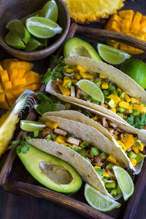 Homemade chicken tacos with mango, ananas and cucumber salsa