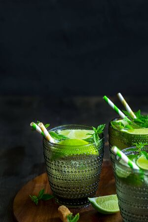 Chilled homemade mojito coctail with lime, mint and brown palm sugar. Copyspace background.