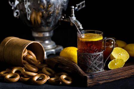 Russian tea in glass with glass holder, samovar, lemon, honey and sushki