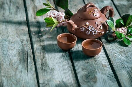 Tea in small brown yixing teapot and spring blossom on old wooden background Фото со стока