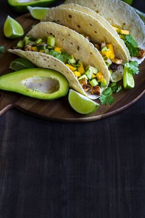 Homemade chicken tacos with mango, ananas and cucumber salsa. Copyspace background. Stock fotó
