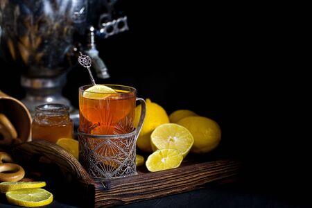 Russian tea in glass with glass holder, samovar, lemon, honey and sushki. Copyspace background.