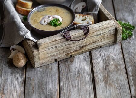Delicious homemade mushrooum soup puree with portobello and wild mushrooms on rustic table. Copyspace background. Stock Photo