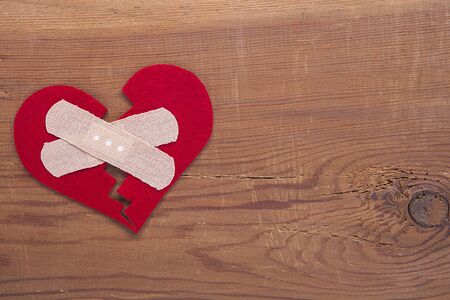 Red broken heart sign on wooden background. Broken heart, love and valentines day concept.