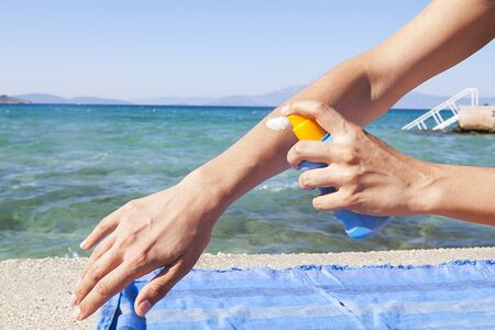 Woman is applying sunscreen on the sunny sandy beach against the blue sea background. The concept of relaxation.