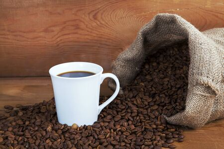 Fresh roasted coffee beans in small bag poured on old rustic wooden surface.