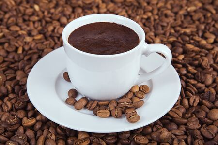 A cup of hot coffee on a wooden table with roasted coffee beans. Turkish coffee. 스톡 콘텐츠