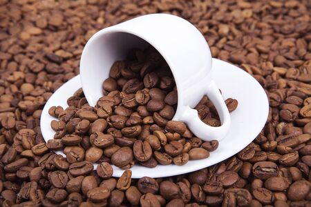 Fresh roasted coffee beans are poured on old rustic wooden surface with coffee cup. 스톡 콘텐츠