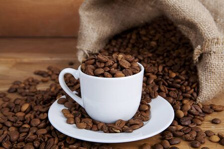 Fresh roasted coffee beans are poured on old rustic wooden surface, with small sack and coffee cup. 스톡 콘텐츠