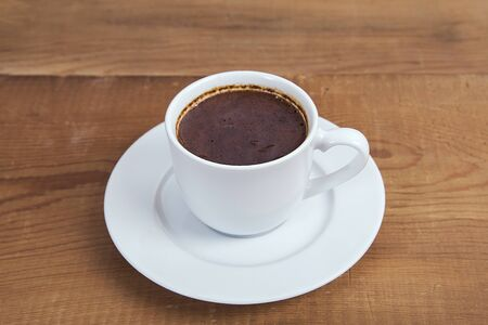 A cup of hot coffee on a wooden table background. Turkish coffee.