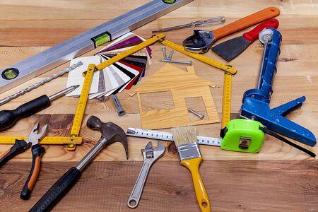 Farbmuster, dekoratives Haus, Holzmesser und Reparaturzubehör auf Holztischhintergrund.