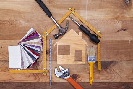 Color samples, decorative house, wood meter and repair supplies on wooden table background. Foto de archivo