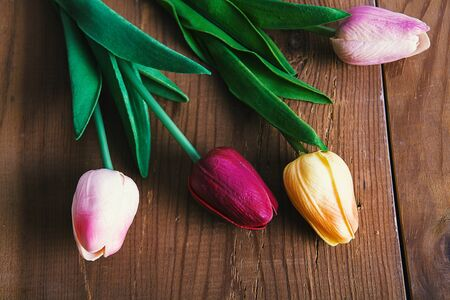 Artificial flowers. Colorful artificial tulips on a wooden background.