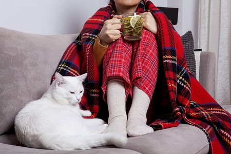 The woman is holding a cup of hot sage. The woman is sick and the weather is cold.